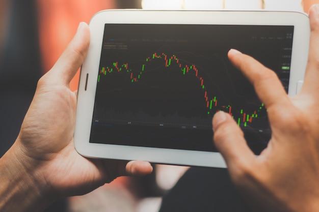 Zakenman die effectenbeurs controleren op een tablet