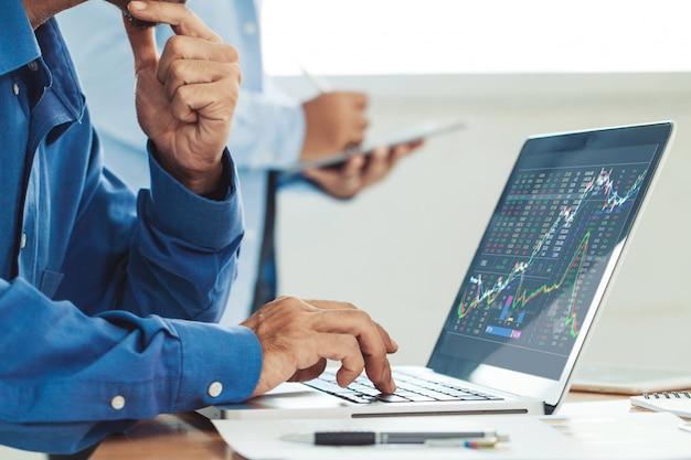Zakenman die effectenbeursrapport en financieel dashboard analyseren met business intelligence, met belangrijke prestatie-indicatoren. ondernemer team dat werkt in creatief kantoor