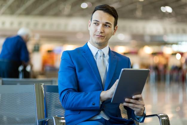 Zakenman die elektronische tablet in een luchthaven gebruikt
