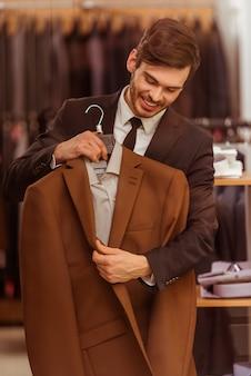Zakenman die en klassiek kostuum in kostuumwinkel kijkt kiest