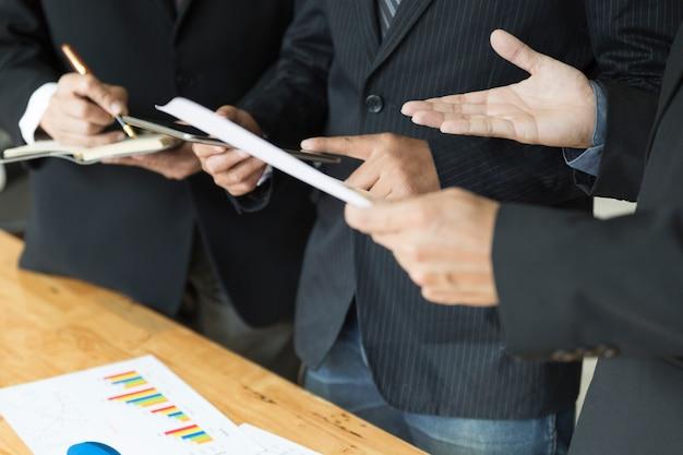 Zakenman die en met tablet en administratiedocument analyseren bespreken