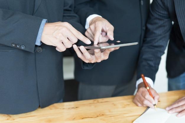 Zakenman die en met tablet en notitieboekje analyseert bespreken