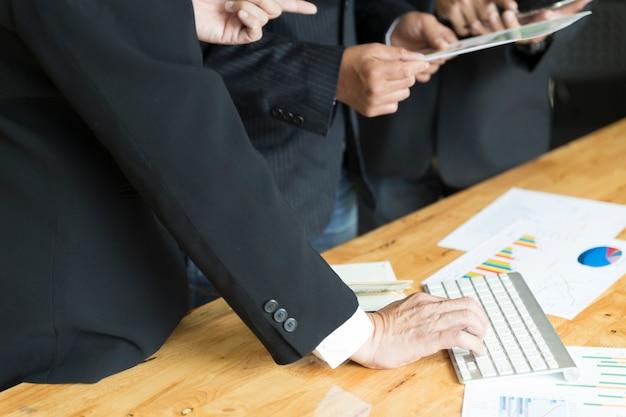 Zakenman die en met toetsenbord en administratiedocument analyseert bespreken