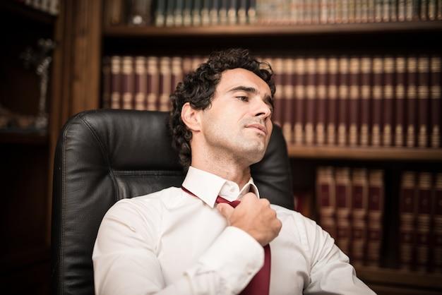 Zakenman die en zijn stropdas ontspant losmaakt