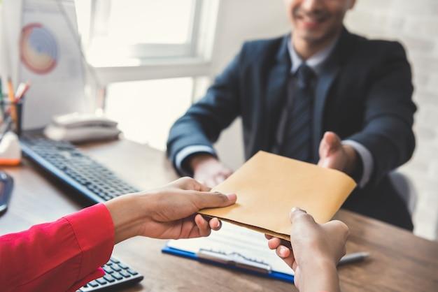 Zakenman die envelop (geld) ontvangt van een vrouw terwijl het maken van contract