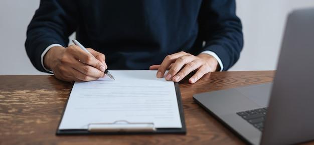 Zakenman die financieel contract en handtekening na het bereiken van overeenkomst ondertekenen.