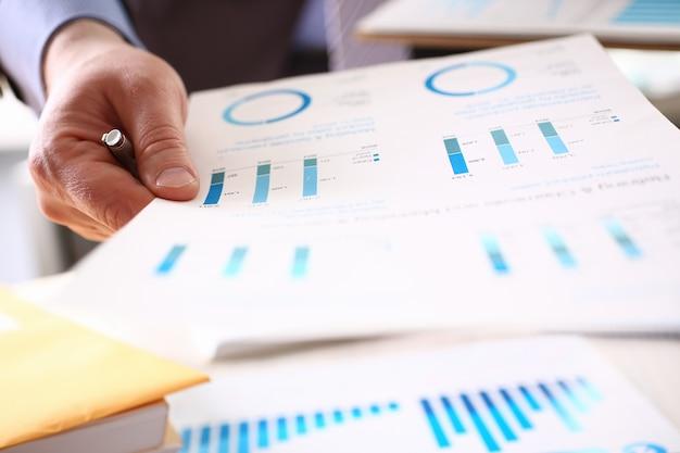Zakenman die financiële grafiek in de hand houdt