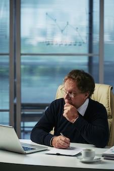 Zakenman die financiële informatie in zijn bureau analyseert