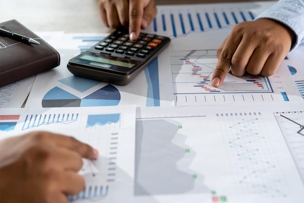 Zakenman die gebruikend een verwezenlijking van het de boekhoudingsconcept van calculatorfinanciën werken om mensen hulpboekhouding in evenwicht te brengen