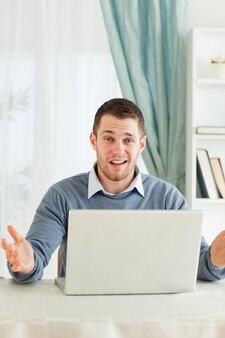 Zakenman die geen idee heeft wat met zijn laptop in zijn homeoffice verkeerd is