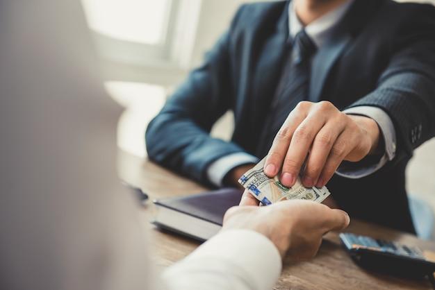Zakenman die geld, amerikaanse dollars, geeft aan zijn partner in het bureau