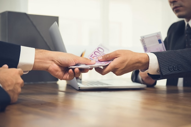 Zakenman die geld, euro bankbiljetten geeft, aan zijn partner op werkend bureau
