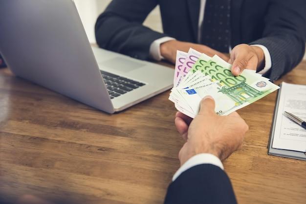 Zakenman die geld, euro bankbiljetten geeft, aan zijn partner terwijl het maken van contract