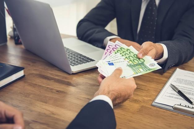 Zakenman die geld, euro bankbiljetten geeft, aan zijn partner terwijl het maken van overeenkomstencontract