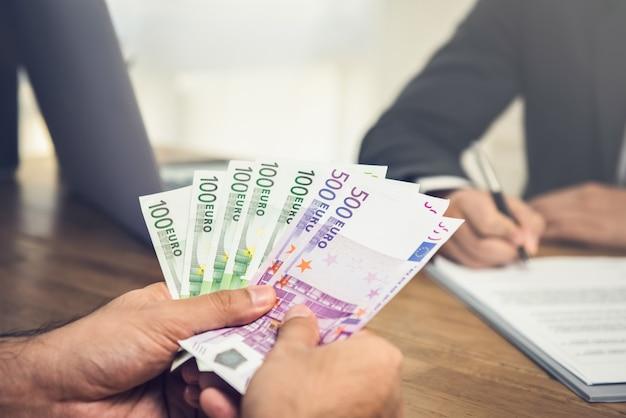 Zakenman die geld, euro munt, aan zijn partner geeft