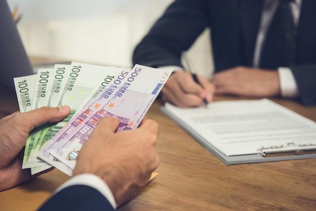 Zakenman die geld, euro munt telt, terwijl het maken van een overeenkomstcontact