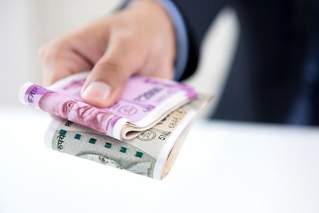 Zakenman die geld geeft in de vorm van indische roepies f