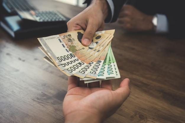 Zakenman die geld geeft, koreaan won bankbiljetten, aan zijn partner