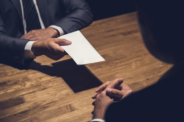Zakenman die geld in de envelop geeft aan zijn partner in dark