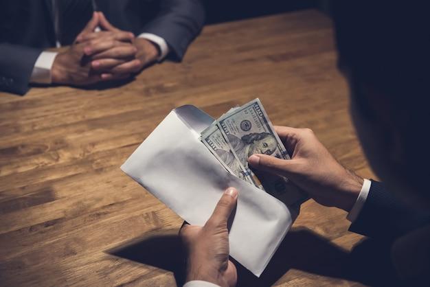 Zakenman die geld in de envelop telt die net door zijn partner wordt gegeven