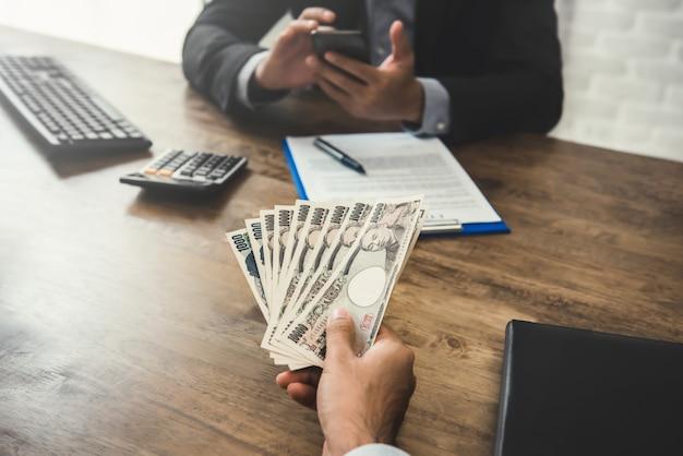 Zakenman die geld, japanse yen-valuta, geeft aan zijn partner
