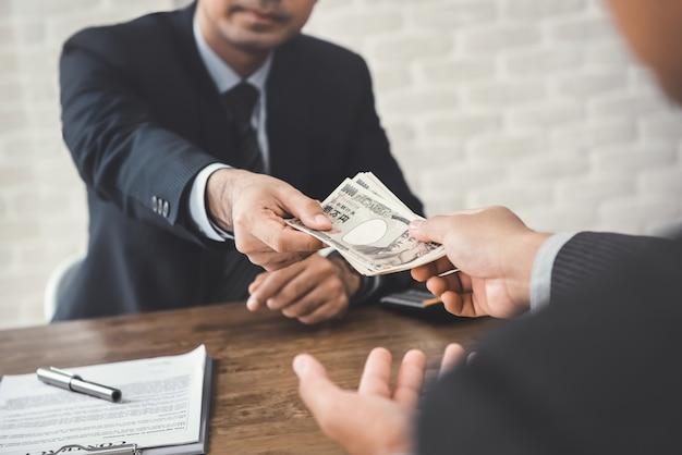 Zakenman die geld, japanse yenbankbiljetten geeft, aan zijn partner na het maken van een overeenkomst