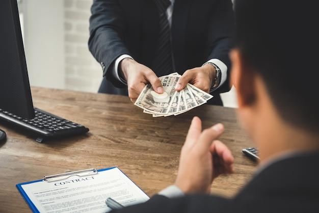 Zakenman die geld, japanse yenbankbiljetten geeft, aan zijn partner terwijl het maken van contract