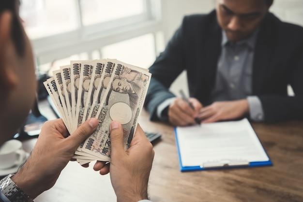 Zakenman die geld, japanse yenbankbiljetten tellen, terwijl het maken van een overeenkomst met zijn partner