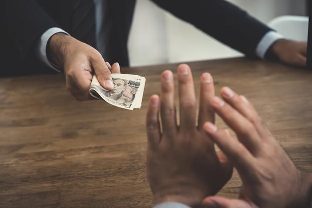 Zakenman die geld, japanse yenbankbiljetten verwerpen - antiomkoping en corruptieconcepten