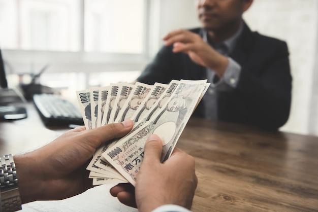 Zakenman die geld, japanse yenmunt geeft, aan zijn partner