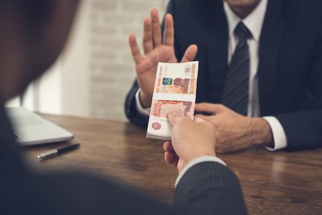 Zakenman die geld, russische roebelmunt weigert, die door zijn partner wordt aangeboden