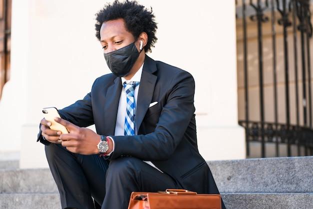 Zakenman die gezichtsmasker draagt en zijn mobiele telefoon gebruikt terwijl hij buiten op de trap zit