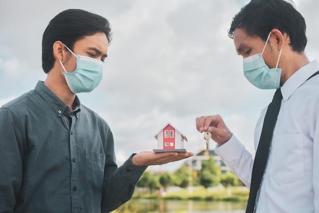 Zakenman die gezichtsmasker draagt, verkoper verkoopt huis aan klant