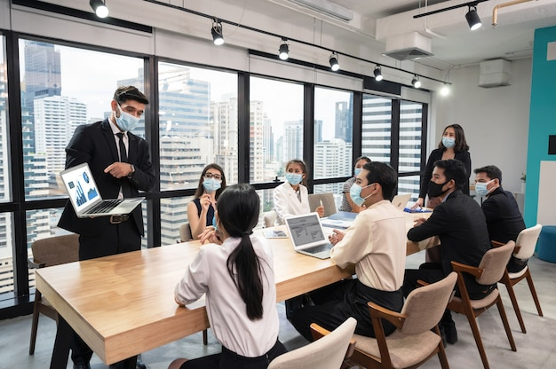 Zakenman die gezichtsmasker met presentatie van businessplan op laptop draagt