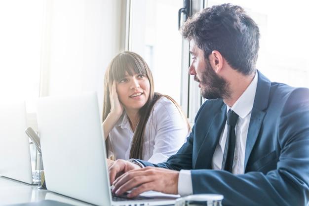 Zakenman die glimlachende jonge vrouw bekijkt die laptop met behulp van