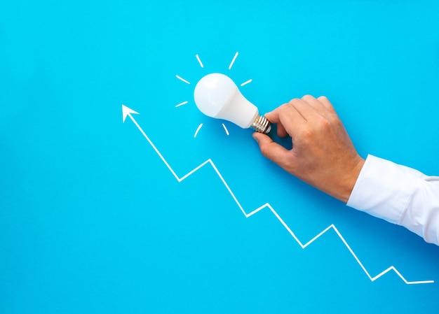 Zakenman die gloeilamp houdt. bedrijfsopstartdoelen voor succes, ontwikkeling en ideeën.