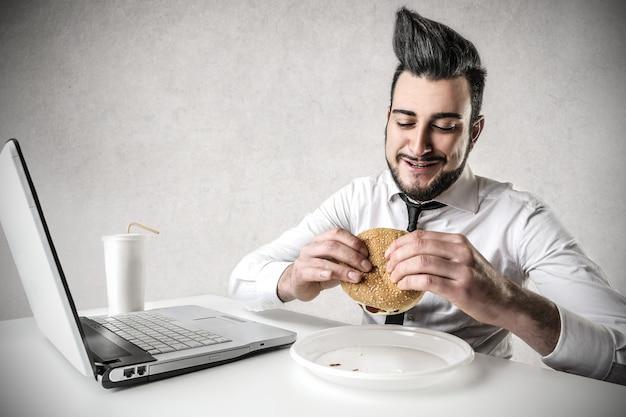 Zakenman die hamburger eet bij zijn bureau