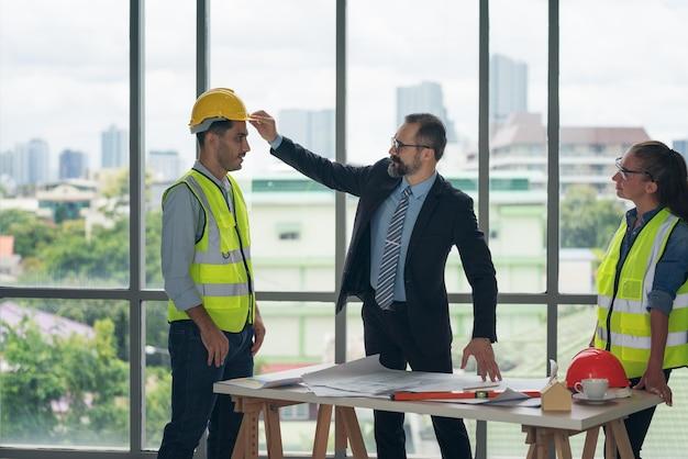 Zakenman die harde veiligheidshelmhoed draagt voor veiligheidsproject van werkman als ingenieur of arbeider