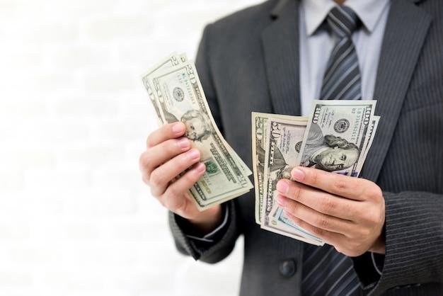 Zakenman die het amerikaanse geld van het amerikaanse dollarsbankbiljet telt