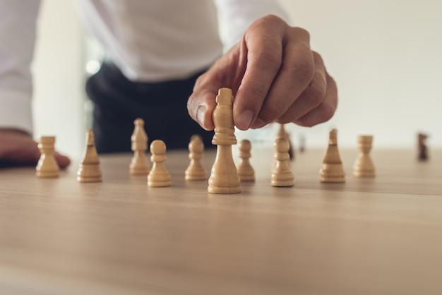 Zakenman die het cijfer van het koningsschaak voorwaarts plaatst