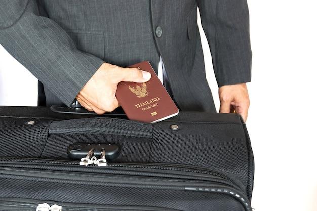Zakenman die het paspoort van thailand met de zwarte koffer houdt