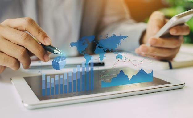 Zakenman die het saldo van het bedrijfs financiële rapport met digitale vergrote werkelijkheidsgrafiek analyseren.