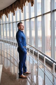 Zakenman die het venster in een reusachtig commercieel centrum bekijkt.