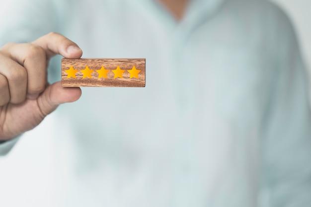 Zakenman die houten kubusblok houdt dat het scherm gele vijf sterren afdrukt. klanttevredenheid en product service evaluatie concept.