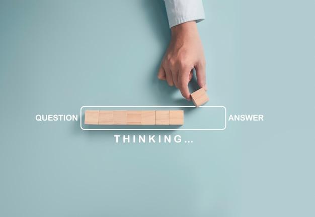 Zakenman die houten kubusblok voor progressieve update tussen vragen en antwoord op blauwe achtergrond zet.