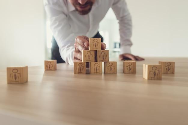 Zakenman die houten kubussen met mensenpictogrammen op bureau stapelt.