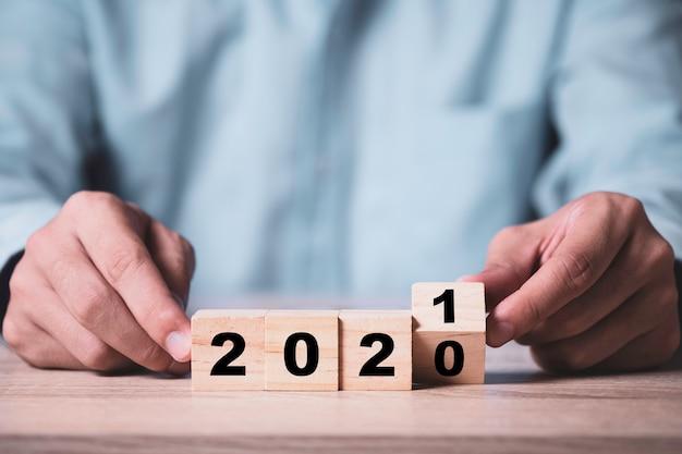 Zakenman die houten kubussenblok wegknipt om het jaar 2020 tot 2021 op houten tafel te veranderen.