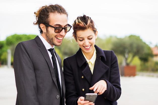 Zakenman die iets in de slimme telefoon toont aan zijn vrouwelijke assistent