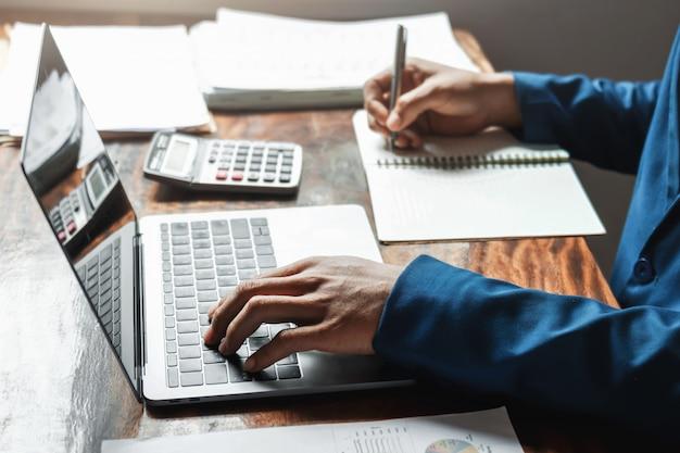 Zakenman die in bureau met het gebruiken van een calculator werkt om het de boekhoudingsconcept van de aantallenfinanciën te berekenen