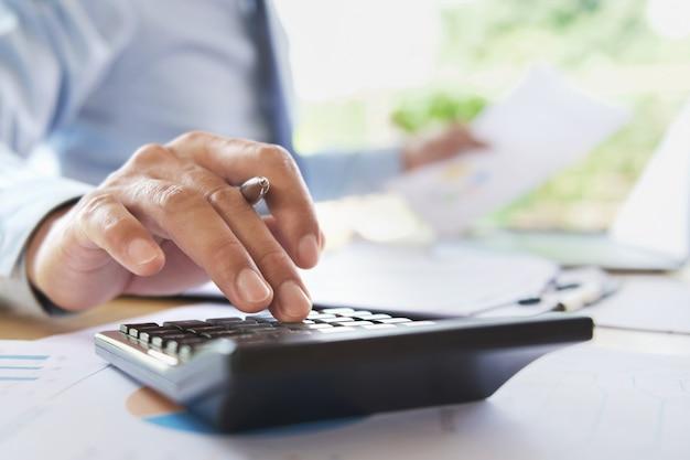 Zakenman die in bureau voor de financiën en de boekhouding van berekeningsgegevens werken